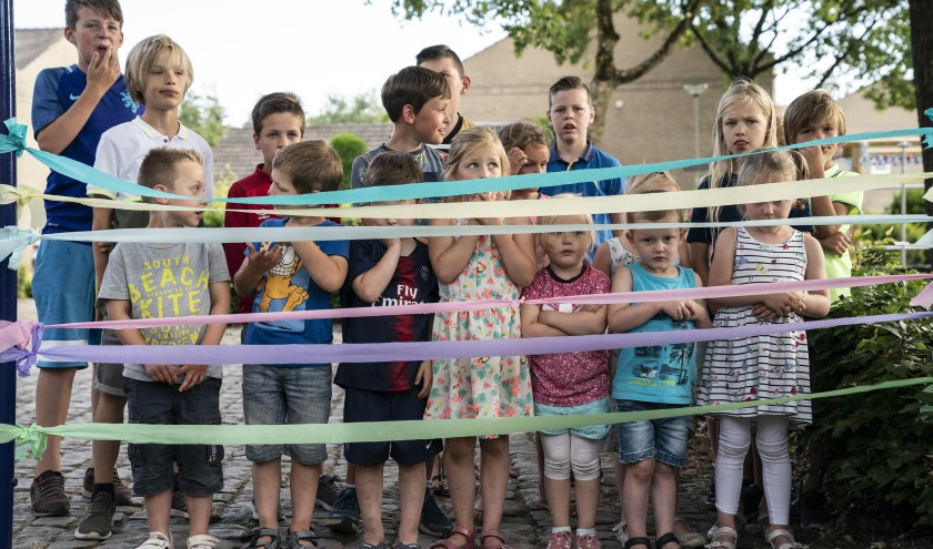 De kinderen wachten tot ze de linten mogen doorknippen en lekker kunnen spelen in de vernieuwde speeltuin.