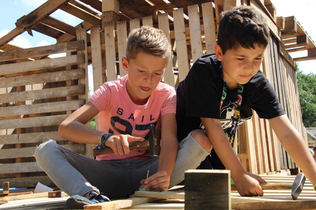 Lars en Christos zijn allebei 8 jaar oud. Ze zijn samen hard aan het werk om het dak te verstevigen.   © Kliknieuws Veghel