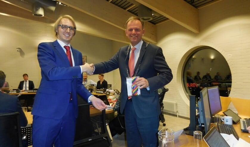 Robin Kersbergen (VVD) overhandigt na het aannemen van de motie voor een inclusieve samenleving een regenboog-stropdas aan de burgemeester