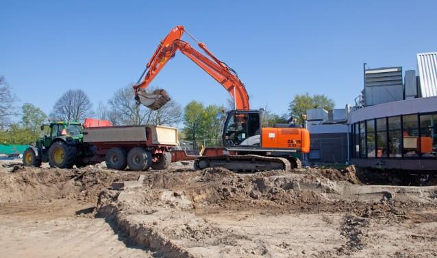 Tractoren rijden af en aan om de grond af te voeren