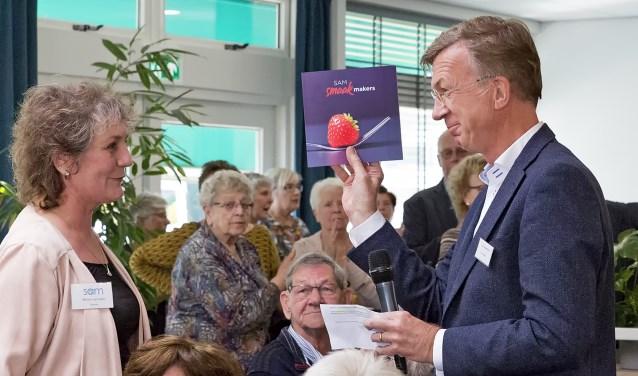 Ron de Haas, directeur Mozaïek Wonen, ontvangt uit handen van Mirjam van Veen, directeur SAM, het eerste exemplaar van het kookboekje dat de medewerkers van SAM hebben samengesteld