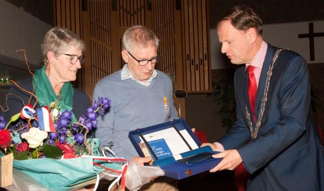 Onder toeziend oog van zijn echtgenote overhandigt burgemeester Van der Kamp de bij de onderscheiding behorende oorkonde aan Hans Rootert