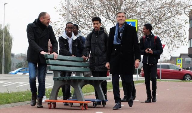 Wethouder Simon Fortuyn verhuist het buitenbankje samen met de leerlingen van Wolfert Lansing.