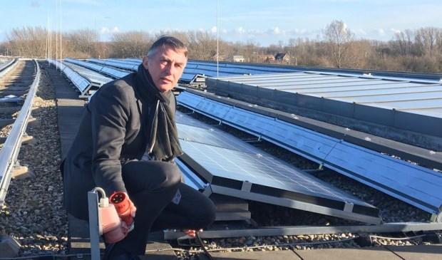 Wethouder Abee bij de zonnepanelen op het dak van het gemeentekantoor.