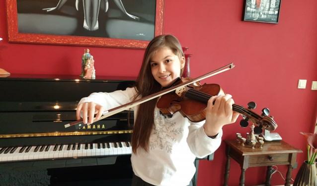 Adinda met haar viool in de huiskamer.