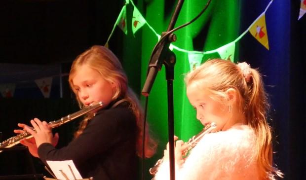 Twee jonge dwarsfluitleerlingen van Hanneke Meijer geconcentreerd bezig op het podium (foto Wim Soeters).