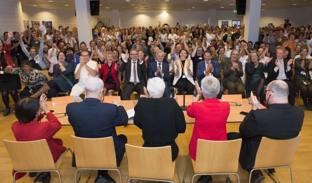 een volle zaal met medewerkers reageert uitgelaten op het moment dat de positieve uitslag bekend wordt gemaakt