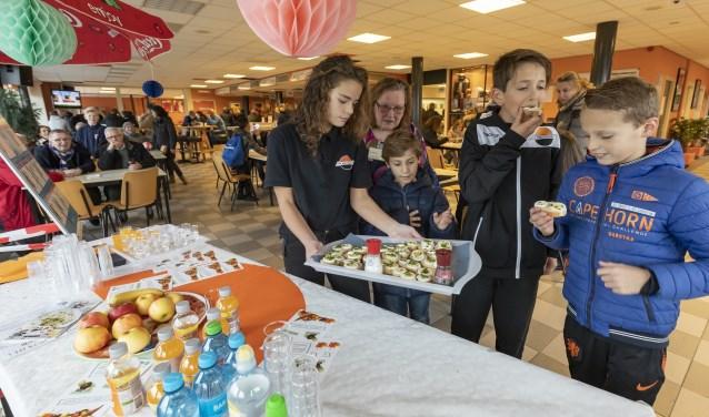 Daphne laat jonge voetballers proeven van gezonde snacks.