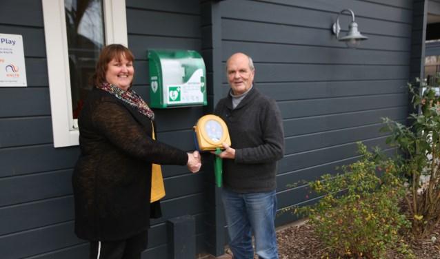 Initiatiefnemer Jacqueline de Keijser en Harry Spermon met de AED bij de nieuwe buitenkast.