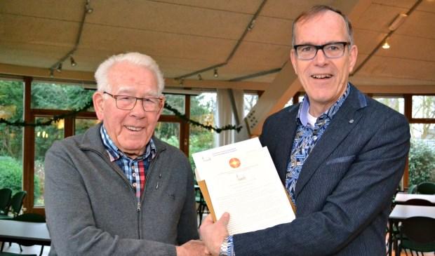 Foto: Kees Vos, voorzitter van de wijkkerkenraad, overhandigt de oorkonde aan Wim Mes.