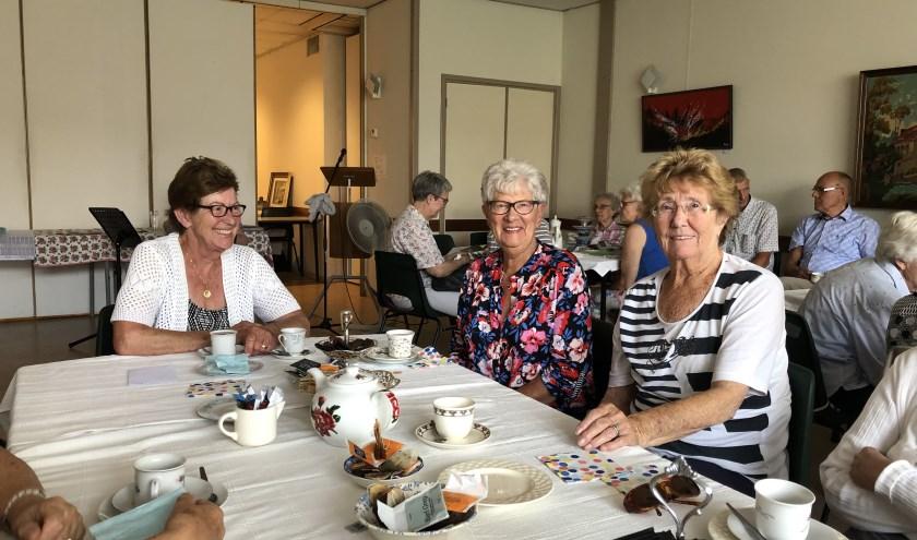 De dames genieten van de high tea en elkaars gezelschap.