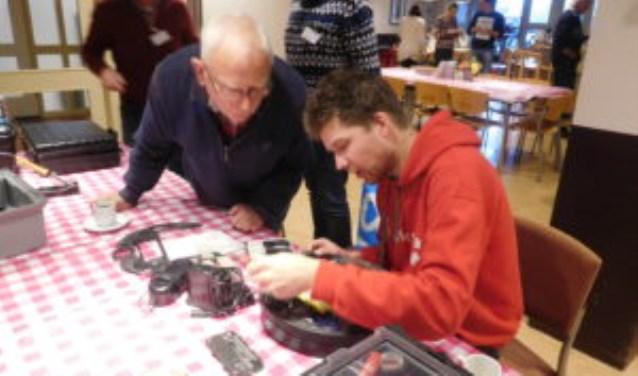Vrijwilligers helpen met reparatie