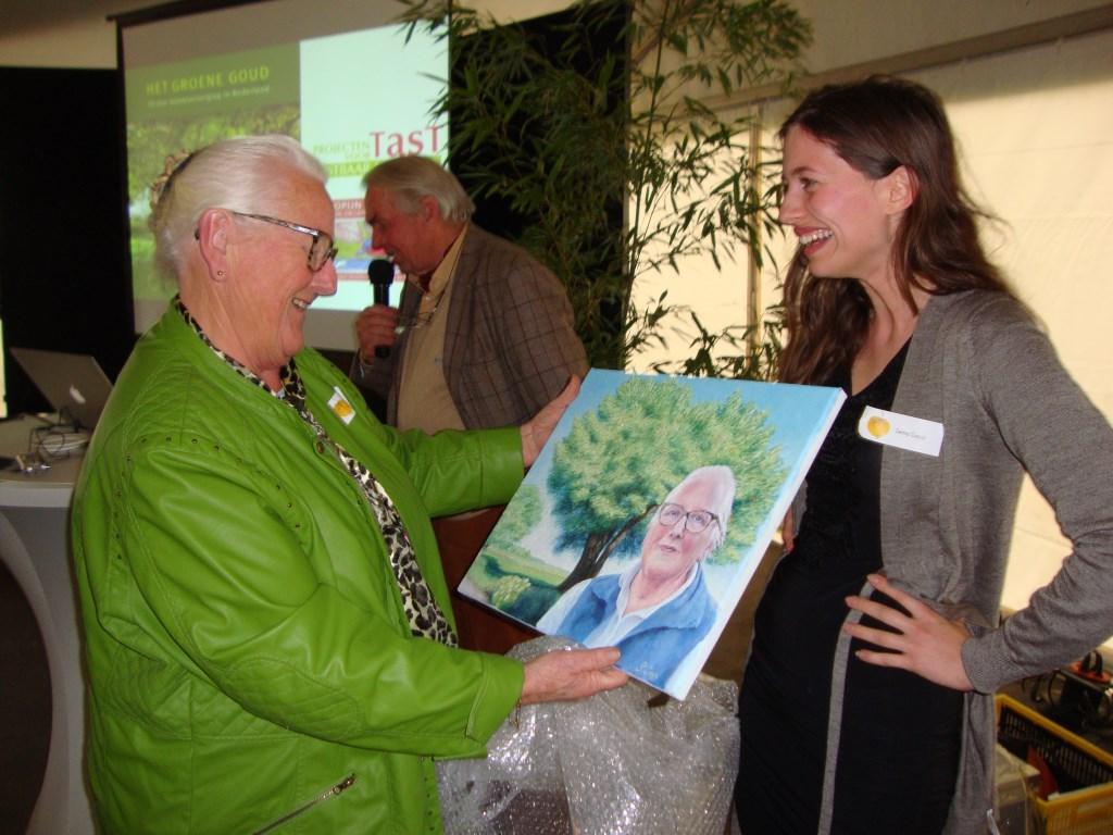 Minie Arissen ontvangt van Selma Copijn een schilderij waarop zij staat afgebeeld bij de duizendjarige linde van Achterberg die op haar op haar erf staat.  © Persgroep