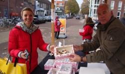 Annelies van Ooijen koopt een doos met cupcakejes van harmonielid Rob van Bergen. Foto: Martin Brink/Rijnpost