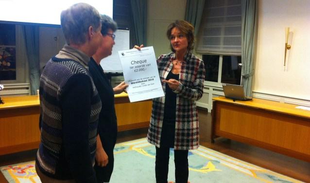 Wethouder Linda van Dort overhandigd de wereldbokaal aan Hanny Peters en Dorien van den Broek van Stichting Stinica. Foto: Naomi Slijngard