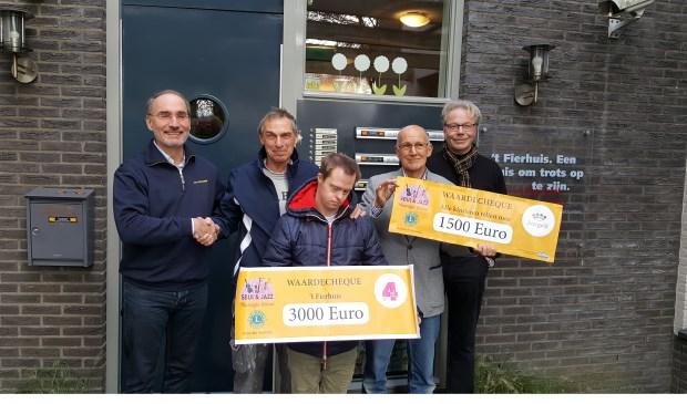 Voorzitter Anton Belt van de Lionsclub Soestdijk overhandigt de cheque aan de voorzitter van 't Fierhuis en aan de voorzitter van afdeling Soest van stichting Leergeld. (Foto: Lionsclub Soestdijk)