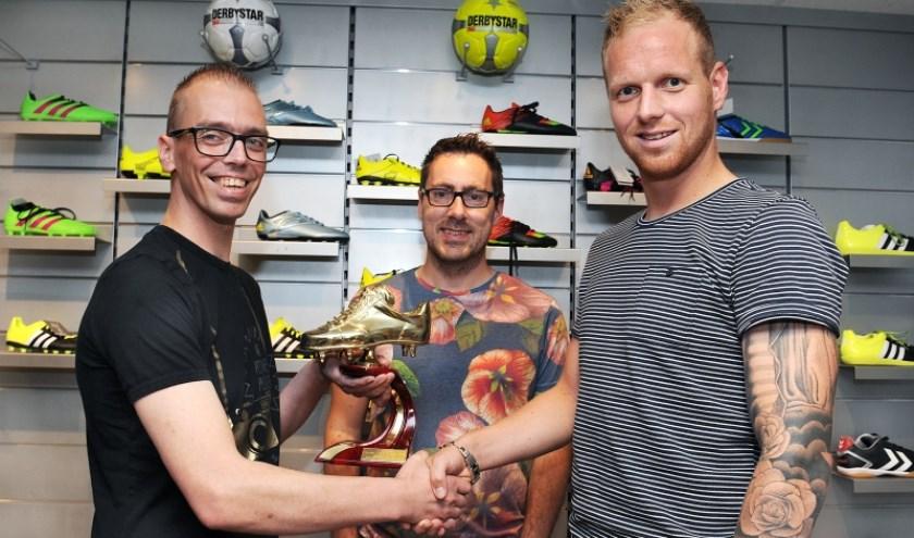 Niels Schweckhorst (rechts) krijgt de Gouden Schoen overhandigd van Rick Benerink (links) onder toeziend oog van Martijn Kraan, eindredacteur van Oude IJsselstreek Vizier. foto: Roel Kleinpenning