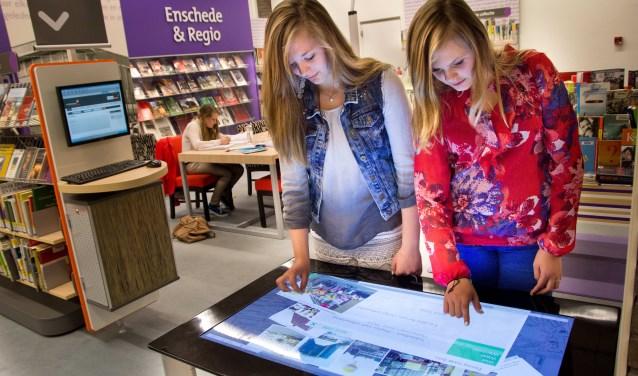 De digitale touchscreen-fototafel staat niet in het archief, maar in de bieb zelf. Hier zijn onder meer zo'n 600 foto's uit het stadsarchief van de gemeente Enschede in te zien. Foto: Bibliotheek Enschede