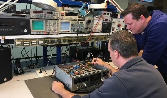 Sander en Frank aan hun 'operatietafel'. Patiënt van de dag: een cassettedeck. Behalve aan audio-apparatuur, schroeven en knutselen de mannen ook aan andere electronische apparaten. Op het moment werken ze aan de camera's van een Vlaams busbedrijf