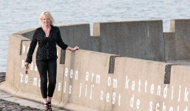 Sandra Burgers is schrijfster van gedichten en creatieve teksten. Hier poseert ze bij een van haar werken: Verliefd slaat ze een arm om Kattendijke heen.  'Zo mooi als jij' zegt de Schelde 'is er geen' FOTO: CARRIE FREDERIKS