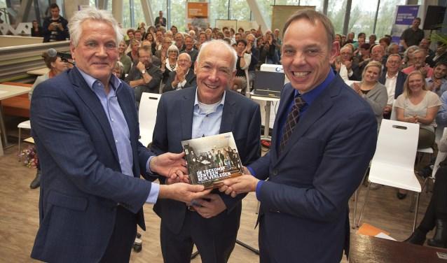 Wethouder Ron Ron König (rechts) ontving maandag 9 oktober het eerste exemplaar van het boek De toekomst kent een rijk verleden over de geschiedenis van het beroepsonderwijs in Arnhem en omgeving van oud-medewerker Peter de Krijger (midden). Links: Ben Geerdink (bestuurder Rijn IJssel). Het boek komt uit ter gelegenheid van het twintigjarig bestaan van Rijn IJssel.