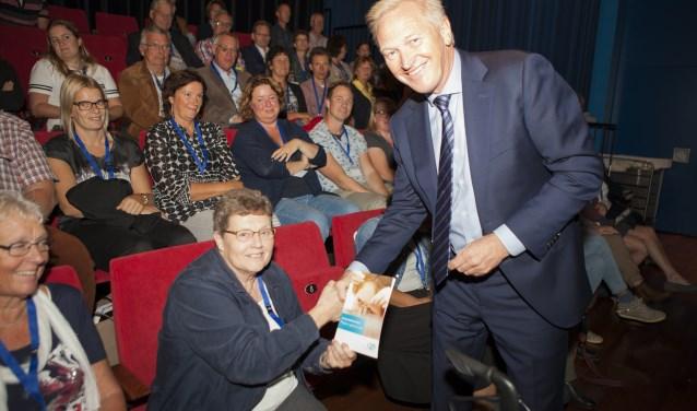 tijdens de bijeenkomst op de Dag van de Armoede overhandigd aan Mevrouw Van Brussel van de Voedselbank ontving het eerste exemplaar van de brochure Inkomensondersteuning uit handen van wethouder Hans van der Velde. (Foto: PR)