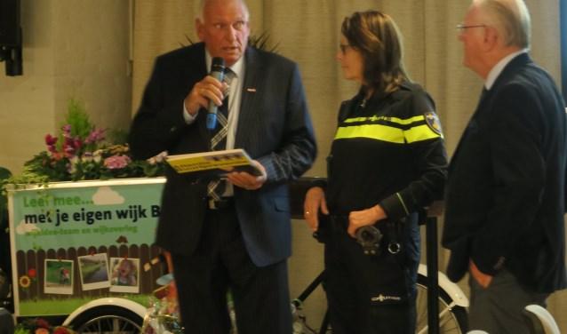 Sarri van der Pol ontvangt uit handen van Toon Huizer (links) het speciaal op de samenwerking tussen politie en buurtpreventie gerichte fotoboek. Rechts Ad Everwijn. (tekst en foto Geert van Someren)