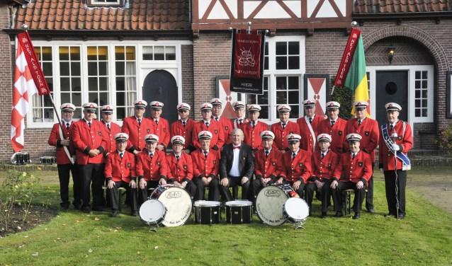 De leden van het jubilerende tamboerkorps NAT in hun herkenbare uniformen, bestaande uit onder andere een rood jasje, zwarte broek en witte pet.
