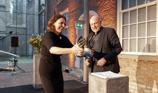 Janelle Moerman ontvangt de handschoenen van André Kuipers.
