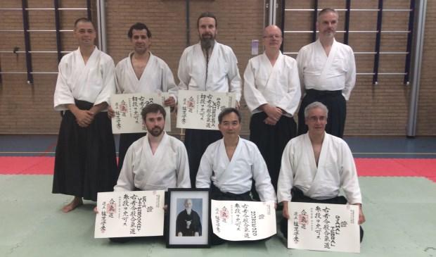 Aikidoka's Houwke Ong (midden voor), Hamid Baqi en Pasi Lahendepera (2e en 3e staand) ontvangen hun Dan-certificaten van hoofdinstructeur Piet Lagerwaard (4e staand).