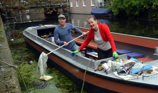 Jan en Lia Persoon van The Hague Boat willen de grachten schoon achterlaten en de mensen erop wijzen hoe vervuilend al die troep in het water is. (Foto: Jos van Leeuwen)