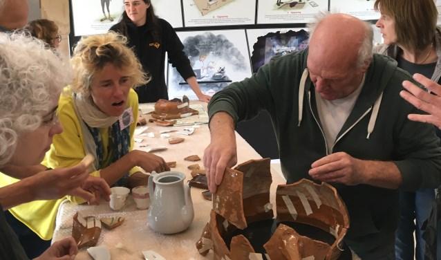 Vrijwilligers puzzelen en plakken de scherven aan elkaar tot - bijna - complete objecten.