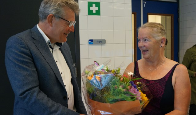 Wethouder Johan Coes overhandigt een bos bloemen aan het 200-ste lid van de Watersoos, mevrouw Geuzendam.