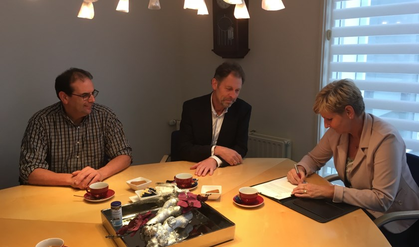 Hendrina Veldhoen zet haar handtekening tijdens het oprichten van de Energie Coöperatie Oldebroek. Mede-bestuursleden Eimert Fikse (links) en Teus Kreuger kijken toe (foto pr).
