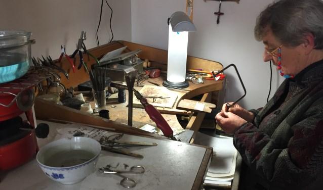Zilversmid Lise Colpa trekt zelf het zilverdraad tot de gewenste dikte en vorm. Ze gebruikt potscherven en stukken oud glas die ze in de moestuin vindt en elk sieraard wordt met veel aandacht gemaakt. FOTO: Ellen van Dilst