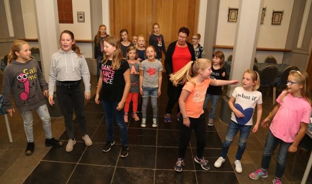 De kinderen van kinderkoor KiKoMi zingen en dansen tijdens een repetitie. (Foto: Marco van den Broek.