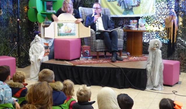 Wethouder Ron König leest voor aan de kinderen in winkelcentrum Kronenburg. (foto: Marnix ten Brinke)