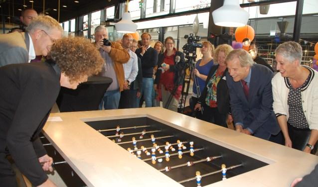 Wethouders Van Huijstee en Weijland en directeuren Poelert en Hopster spelen een potje tafelvoetbal.