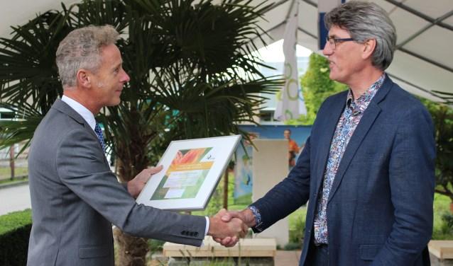 V.l.n.r. directeur VHG Egbert Roozen overhandigt het certificaat aan Hans Kroekenstoel, werkveldleider Tuin & landschap. (foto: Mathijs Geltink)