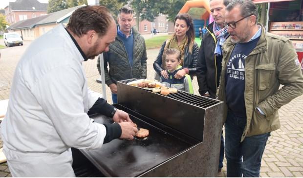Chef-kok Richard Merks, gebogen over een buitengrill, bakt biologische hamburgers.
