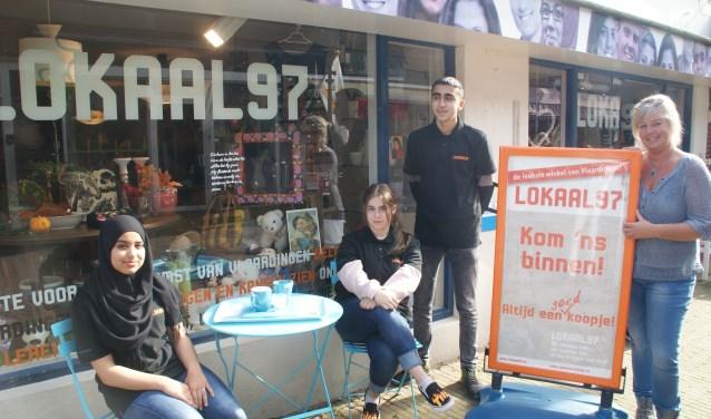 De drie stagiaires met van links naar rechts Rajae, Xaviera en Vagan met docente Annette Wielaard voor de winkel met tweedehands artikelen op de Hoogstraat. (Foto: Peter Spek)