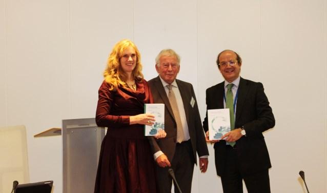 Directeur generaal van DG Environment, Europese Commissie, Daniel Calleja Crespo en Harriët Tiemens, wethouder van de gemeente Nijmegen, nemen de eerste twee boeken van schrijver Ad Lansink in ontvangst. (Foto: Michelle Stuiver)