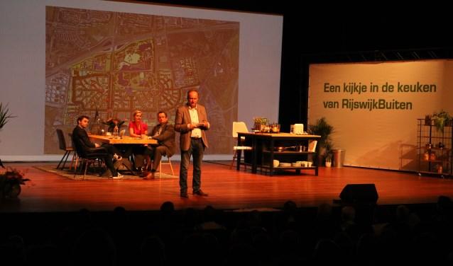 RijswijkBuiten directeur informeert de zaal over de plannen. De wethouders Marloes Borsboom en Ronald van der Meij (r) en presentator Joey (l) luisteren toe. Foto: Otaweb