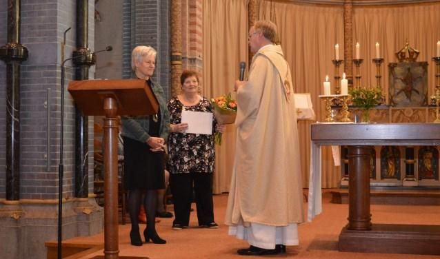 Rinie Renkens-Gerrits 40 jaar koorlid, Annemie Jansen-Vercoulen 12,5 jaar koorlid en pastor Aloys 12,5 jaar pastoor van de parochie.