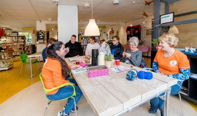 """Herma Lubbers (rechts) met bezoekers van de Huiskamer van de Wijk in de bieb van Twekkelerveld: """"Als bieb heb je de taak om middenin de maatschappij te staan."""""""
