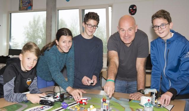 Docent Ronald Mulder samen met leerlingen aan de slag met programmeren.