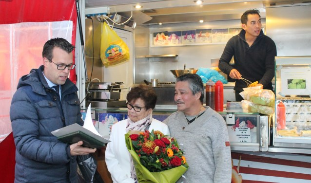 Wethouder Derk Alssema overhandigde de originele aanvraag voor een staanplaats aan het echtpaar Lam met in de kraam neef Hai Nguen, die de verkoop voortzet.. foto Leon Janssens