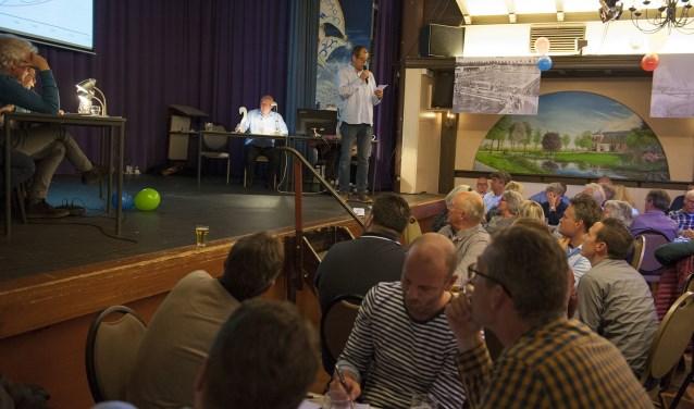 Wes Leurs is de presentator van de dorpsquiz in Het Wapen van Elst. De deelnemers kijken voor een van de vragen naar het scherm. In de zaal waren foto's opgehangen van Elst uit vroegere tijden. (foto: Ellen Koelewijn)