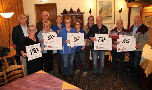 De vertegenwoordigers van de maatschappelijke doelen met de symbolische cheques die zij ontvingen van de organisatie van de Kerstmarkt in Vaassen. (foto: Arrien Scholten)