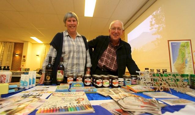 Elly en Dik Vergunst achter de tafel met producten uit in Israël. Met enkele andere vrijwilligers zorgen ze ervoor dat de winkel met de naam De Bron twee keer per week geopend is. (foto: Kirsten den Boef)